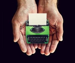 green typewriter in hands